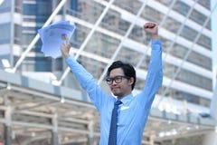 Retrato del hombre de negocios asiático joven acertado que aumenta las manos con las cartas o papeleo en el fondo urbano de la ci Fotografía de archivo