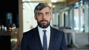 Retrato del hombre de negocios atractivo del hombre que mira la situación de la cámara en café almacen de video