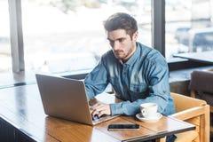 Retrato del hombre de negocios barbudo serio acertado joven que trabaja en el ordenador que se sienta en oficina foto de archivo