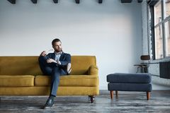 Retrato del hombre de negocios barbudo y hermoso en el traje de la moda que está descansando sobre el sofá en una oficina moderna fotos de archivo libres de regalías
