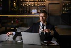 Retrato del hombre de negocios caucásico elegante hermoso que trabaja en su ordenador portátil y café de consumición en restauran imagenes de archivo