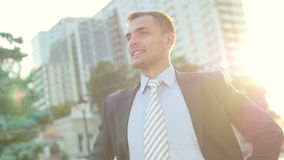 Retrato del hombre de negocios confiado atractivo que se coloca antes del edificio de oficinas