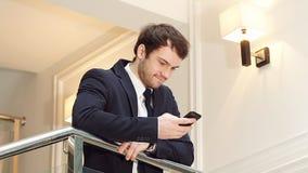 Retrato del hombre de negocios confiado joven con smartphone en oficina moderna almacen de video