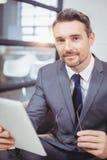 Retrato del hombre de negocios confiado que sostiene la tableta digital mientras que se sienta en el sofá imagen de archivo