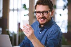 Retrato del hombre de negocios confiado usando el teléfono móvil en la oficina fotografía de archivo libre de regalías