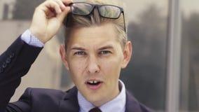Retrato del hombre de negocios dado una sacudida el?ctrica Hombre caucásico hermoso joven en vidrios de los lanzamientos de la so almacen de video