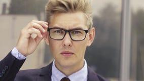 Retrato del hombre de negocios dado una sacudida el?ctrica Hombre caucásico hermoso joven en vidrios de los lanzamientos de la so almacen de metraje de vídeo