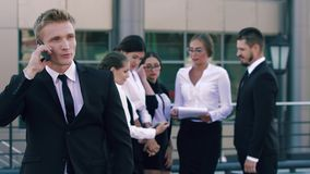 Retrato del hombre de negocios de la Smart-ciudad que habla en el teléfono y los hombres de negocios en fondo que discuten a la c almacen de video