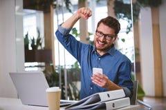 Retrato del hombre de negocios emocionado que perfora en aire en la oficina foto de archivo