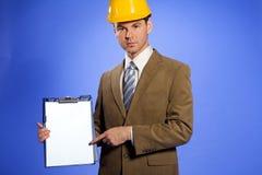 Retrato del hombre de negocios en el casco de protección que señala en el tablero fotos de archivo