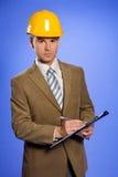 Retrato del hombre de negocios en la escritura amarilla del casco de protección en el tablero fotografía de archivo libre de regalías