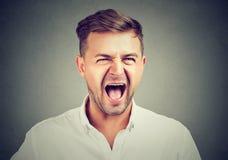 Retrato del hombre de negocios enojado joven que grita imagenes de archivo