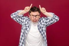 Retrato del hombre de negocios envejecido medio enojado en camisa a cuadros casual y las lentes que se colocan con los cuernos de fotos de archivo libres de regalías