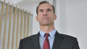 Retrato del hombre de negocios envejecido medio serio en oficina almacen de video