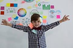 Retrato del hombre de negocios feliz con las notas pegajosas que se oponen a whiteboard en oficina fotos de archivo