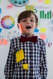 Retrato del hombre de negocios feliz con las notas pegajosas sobre cara en oficina foto de archivo