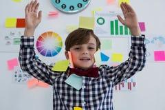 Retrato del hombre de negocios feliz con las notas pegajosas sobre la cara que se opone a whiteboard en oficina Imagen de archivo libre de regalías