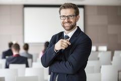Retrato del hombre de negocios feliz que se coloca en pasillo del seminario Fotos de archivo