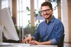 Retrato del hombre de negocios feliz que trabaja en el ordenador en la oficina creativa imagen de archivo libre de regalías