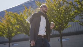 Retrato del hombre de negocios hermoso caucásico en vidrios que camina en la calle cerca del edificio de oficinas, café de consum almacen de video