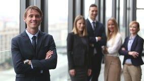 Retrato del hombre de negocios hermoso que sonríe, colegas en fondo metrajes