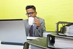 Retrato del hombre de negocios indio que sostiene la taza y que trabaja en su ordenador portátil en su escritorio Fotos de archivo