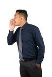 Retrato del hombre de negocios joven Asian Man Whispering, por ejemplo, que habla, susurro, boca abierta de la mano del control c Fotografía de archivo libre de regalías