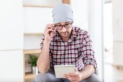 Retrato del hombre de negocios joven del inconformista que se sienta en la oficina y que usa la tableta digital foto de archivo libre de regalías