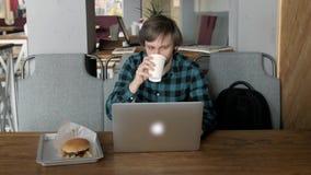 Retrato del hombre de negocios joven ocupado que se sienta con el vidrio de la bebida y la hamburguesa en interior del restaurant almacen de video