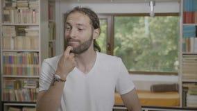 Retrato del hombre de negocios joven pensativo que tiene una búsqueda de pensamiento del dilema para las ideas que tocan su barba metrajes