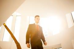 Retrato del hombre de negocios joven que camina en la escalera foto de archivo libre de regalías