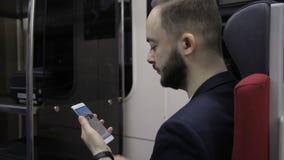 Retrato del hombre de negocios joven, que está leyendo noticias económicas en el tren almacen de video