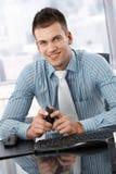 Retrato del hombre de negocios joven que se sienta en el escritorio Imagen de archivo