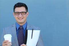 Retrato del hombre de negocios joven sonriente feliz con un traje, un lazo y vidrios clásicos contra fondo azul Imagen de archivo