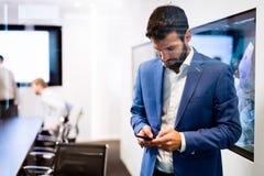 Retrato del hombre de negocios joven usando el teléfono móvil Fotografía de archivo libre de regalías