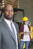 Retrato del hombre de negocios masculino afroamericano confiado con el trabajador de sexo femenino que se coloca en fondo fotografía de archivo libre de regalías