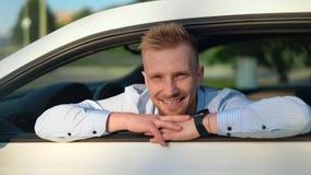 Retrato del hombre de negocios masculino hermoso que presenta en el coche deportivo de lujo blanco que mira a través de ventana a almacen de video