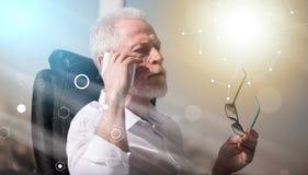 Retrato del hombre de negocios mayor barbudo que habla en el teléfono móvil, efecto luminoso, sobrepuesto con la red imagen de archivo