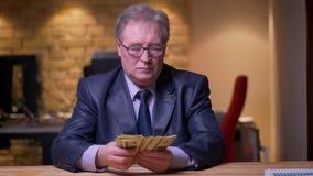 Retrato del hombre de negocios mayor en el traje formal que cuenta el dinero que es concentrado y atento en oficina almacen de video