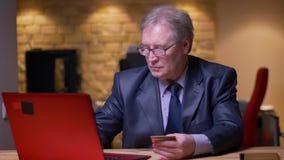 Retrato del hombre de negocios mayor en el traje formal que hace transacciones con la tarjeta de cr?dito y el ordenador port?til  almacen de video
