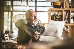 Retrato del hombre de negocios mayor que se sienta en su oficina, librando el ne imagenes de archivo