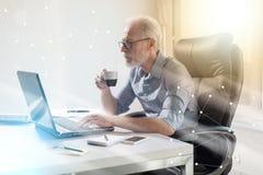 Retrato del hombre de negocios mayor que trabaja en el ordenador portátil, efecto luminoso, sobrepuesto con la red imágenes de archivo libres de regalías