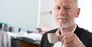 Retrato del hombre de negocios mayor sonriente con una taza de café Fotografía de archivo