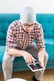 Retrato del hombre de negocios moderno que se sienta en sofá y que mira la tableta digital imagenes de archivo