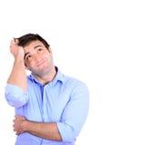 Retrato del hombre de negocios pensativo joven que rasguña el isolat principal Imagen de archivo