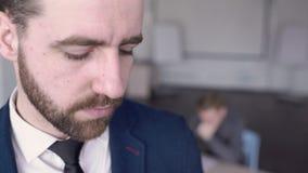 Retrato del hombre de negocios que está leyendo informe en la oficina almacen de metraje de vídeo