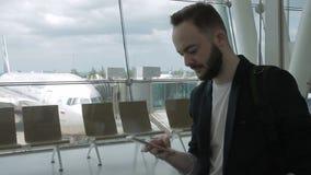 Retrato del hombre de negocios que está mecanografiando el messege en su smartphone dentro del aeropuerto almacen de metraje de vídeo