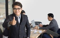 Retrato del hombre de negocios que se coloca delante de su equipo en la oficina, hombre de negocios asiático que lleva a su equip imagen de archivo libre de regalías