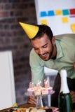Retrato del hombre de negocios que sopla hacia fuera las velas para su cumpleaños Fotos de archivo