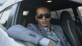 Retrato del hombre de negocios serio en las gafas de sol que se sientan dentro del coche y que miran en cámara al aire libre